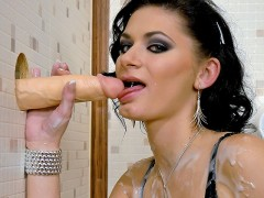 Slutty brunette is checking her make up in a menÂ's room when she spies something sticking out of a gloryhole. She approaches cautiously but soon grabs this huge fake cock and decides to have some fun, she jerks and sucks on it before it literally unleashes a floor of fake spunk. She gets absolutely coated in the stuff and by the end you cant see her actual face at all!video